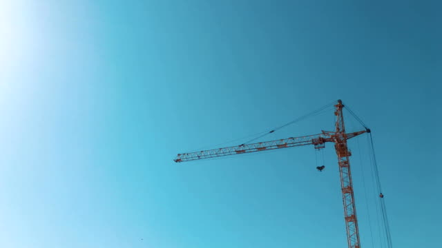 High-rise building, crane, blue sky, white clouds in the light of the setting sun - vídeo