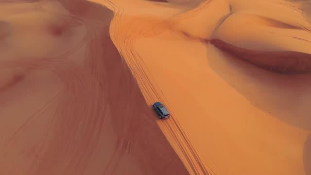 AERIAL. Hight flight above car. Desert safari car sand dunning in the Dubai desert during sunset