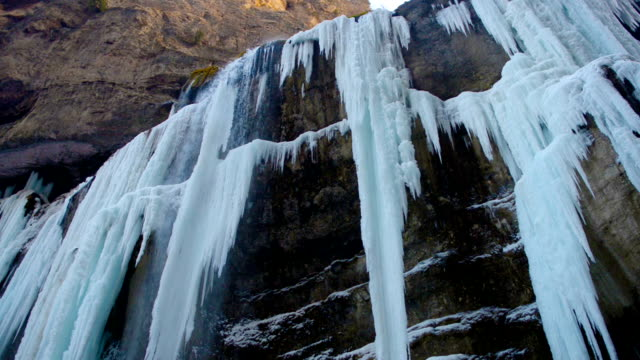 hight frozen waterfall with ice in blue and white color in winter video