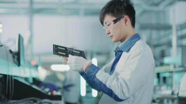 ハイテク工場: 品質管理エンジニア チェック電子プリント基板のそれ損害賠償。pcb 表面マウント ピックアップやプレイスのテクノロジーと共に背景組立ラインで。 - 半導体点の映像素材/bロール