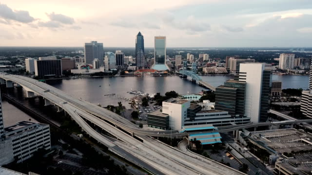 Highway 95 Cuts Through Downtown Jacksonville Florida Light traffic exists before sunset in Jacksonville, Florida in this aerial view with St Johns River florida us state stock videos & royalty-free footage