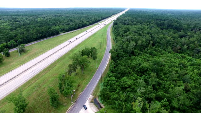 Highway cutting right through a thick Forest Aerial View East Texas video