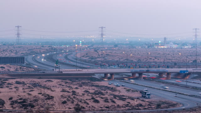 Highway roads with traffic day to night timelapse in a big city from Ajman to Dubai before sunset. Transportation concept video