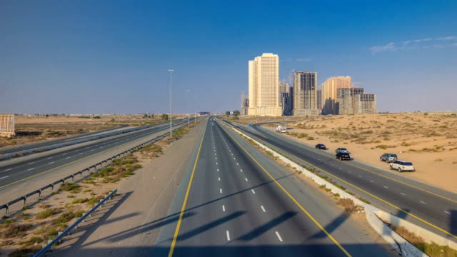 Highway roads with traffic timelapse in a big city from Ajman to Dubai before sunset. Transportation concept video