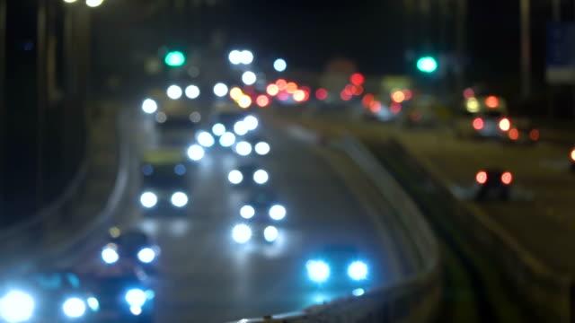 autobahn-verkehrsautos in der nacht. schwenken sie über den hintergrund der stadt unscharf. bewegende bokeh-kreise des nachtverkehrs. autos, die am brückenabend auf der straße unterwegs sind. autobahn im dunkeln. - gold waschen stock-videos und b-roll-filmmaterial