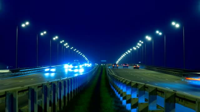 highway traffic bilar på natt tid förfaller. bilar rör sig på väg på bridge kväll timelapse. 4k uhd - diabild bildbanksvideor och videomaterial från bakom kulisserna
