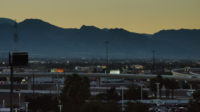 highway traffic entering las vegas at dusk - città diffusa video stock e b–roll