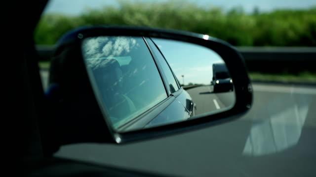 Highway traffic, rear-view mirror Highway traffic, rear-view mirror rear view mirror stock videos & royalty-free footage