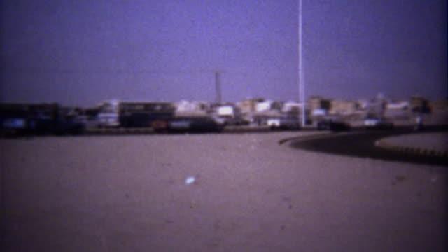 1974: Highway traffic tour bus driving barren desert landscape.