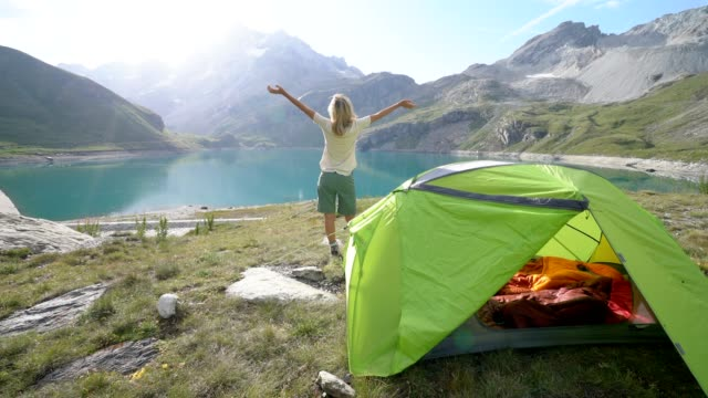 Hiker arms wide open in nature surrounded by scenic mountain lake landscape video