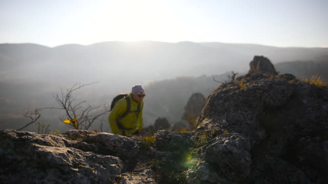 Hiker climbing to the mountain top on sunny autumn day video