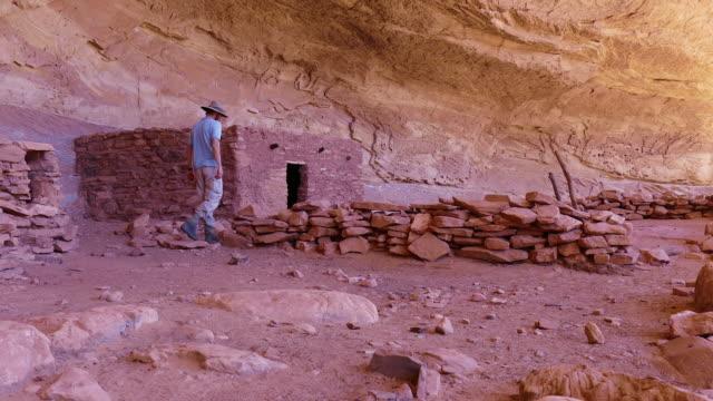 Hiker enjoys exploring Cedar Mesa Pueblo ruins Grand Gulch Utah video