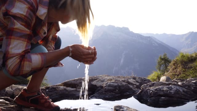 Hiker female drinking water on mountain trail from fresh stream