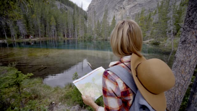 Hiker female looking at map near mountain lake video