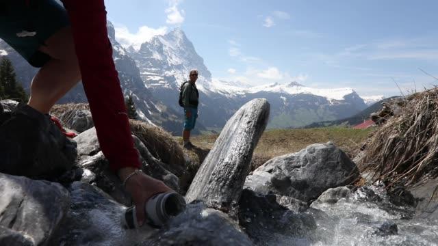 hiker fyller vatten flaska medan följeslagare ser - grindelwald bildbanksvideor och videomaterial från bakom kulisserna