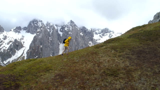 hiker goes on a hill against the background of snow-capped mountains