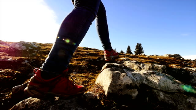 hiker hiking at sunny day on mountain expressing freedom, health, sportiness and adventure. - pietra roccia video stock e b–roll