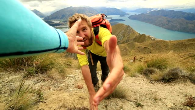 Hiker hiking pulls out hand to get assistance from teammate