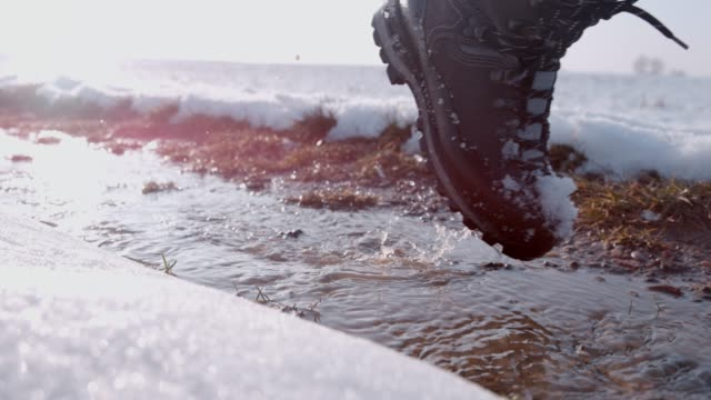 Hiker in boots walking in snow and slush on winter road, super slow motion 4K Hiker in boots walking in snow and slush on winter road. CU, super slow motion. stepping stock videos & royalty-free footage
