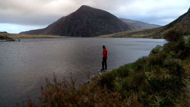 Hiker makes his way through rugged highland environment admiring the views