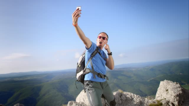 PAN hiker making crazy selfies on the mountain top video