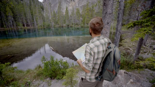 Hiker male looking at map near mountain lake video