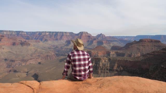 ein wanderer-mann sitzt, einen atemberaubenden blick auf den grand canyon allein beobachtet - landscape crazy stock-videos und b-roll-filmmaterial