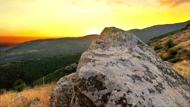Hiker pov slow moving over mountain rock toward sunset orange sky video