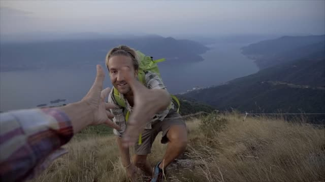 hiker pulls out hand to get assistance from teammate at the top of the mountain to reach summit - fiducia video stock e b–roll