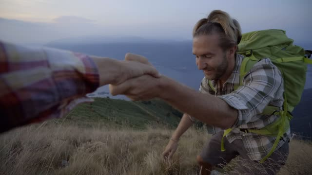 Hiker pulls out hand to get assistance from teammate at the top of the mountain to reach summit