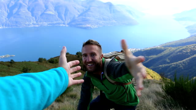 Alpinista puxa para fora de mão para obter assistência do companheiro de equipa - vídeo