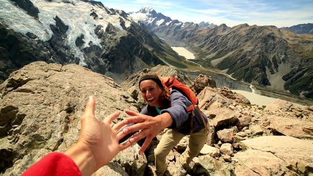 da hiking mostra la sua mano per ottenere assistenza dal compagno di squadra - fiducia video stock e b–roll
