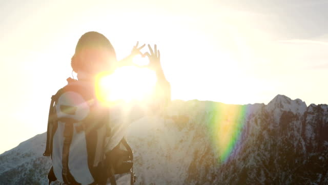 Hiker reaches mountain summit, makes heart shape with hands video