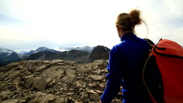 vídeos y material grabado en eventos de stock de excursionistas llega a la cima de la montaña, los brazos estirados - escalada en rocas