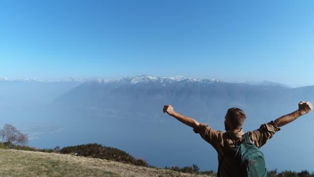 vídeos de stock e filmes b-roll de hiker reaches mountain top, arms outstretched - lago maggiore
