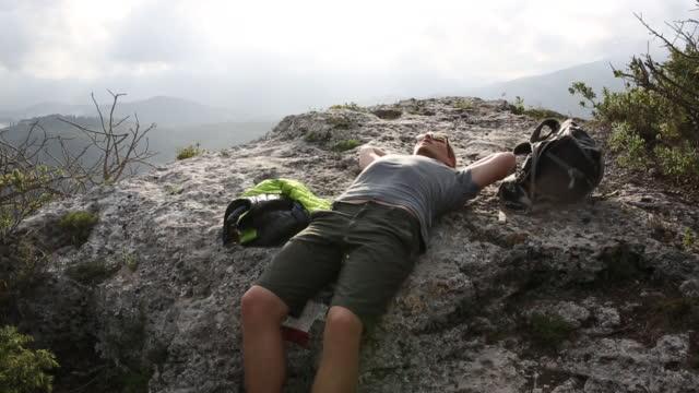 vidéos et rushes de randonneur détend sur le rebord de pierre, au-dessus de la vallée, les collines lointaines - allongé sur le dos
