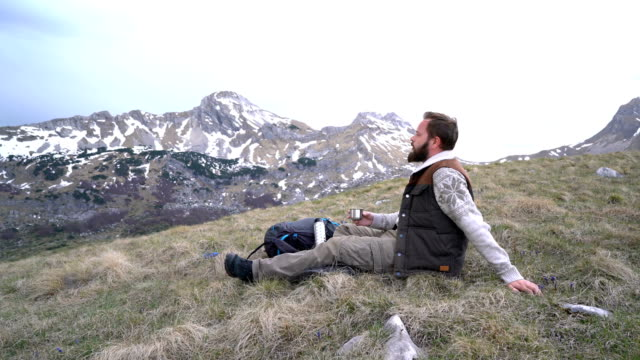 Hiker sits and drinks hot tea from a thermos video