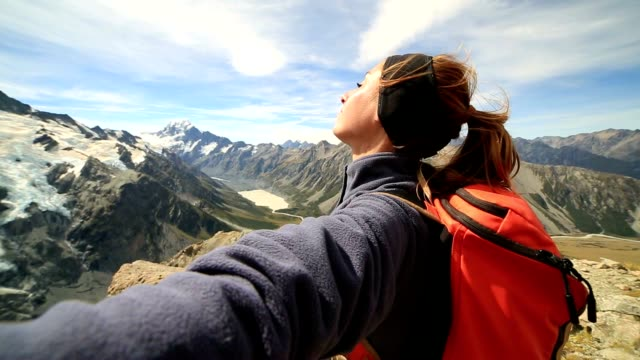 Hiker stands on a mountain top arms outstretched video