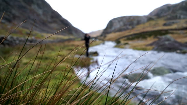 Hiker takes photo of beautiful highland stream