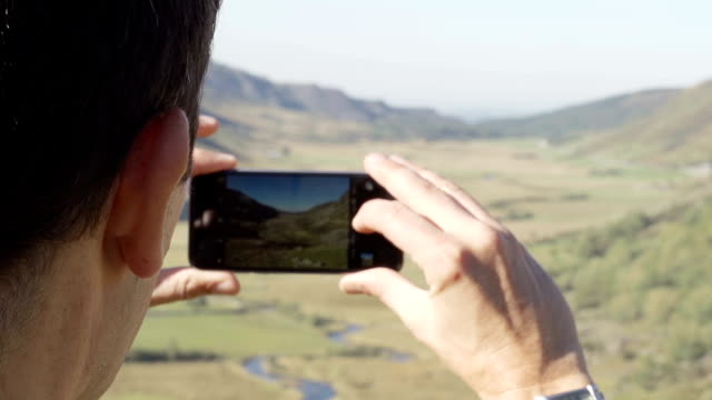 Hiker Taking A Photograph Overlooking Pretty Valley video