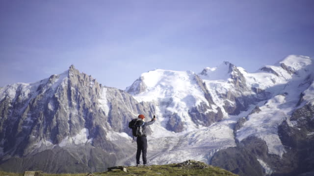 hiker taking a selfie near mont blanc - grandangolo tecnica fotografica video stock e b–roll