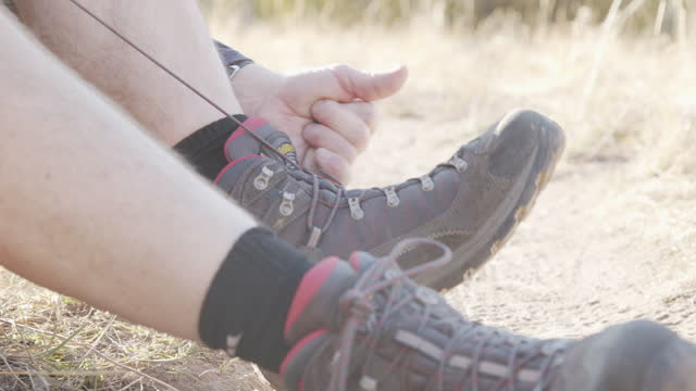 Hiker Ties Shoelaces on His Hiking Boots on an Adventure in the Grand Mesa National Forest near Grand Junction Colorado in the Beautiful September Fall Colors