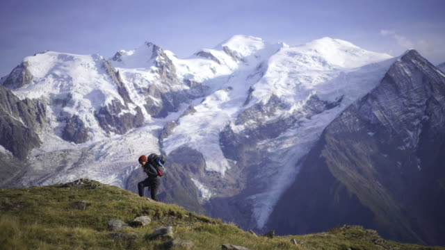 hiker walking along a path near mont blanc - monte bianco video stock e b–roll