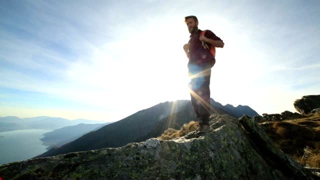 Hiker walks along mountain ridge crest at sunset video