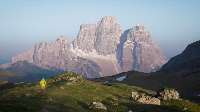 hiker walks down alpine meadow ridge at sunrise - grandangolo tecnica fotografica video stock e b–roll