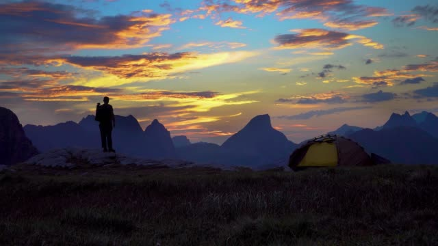 Hiker with backpack enjoys a beautiful sunrise in the mountains