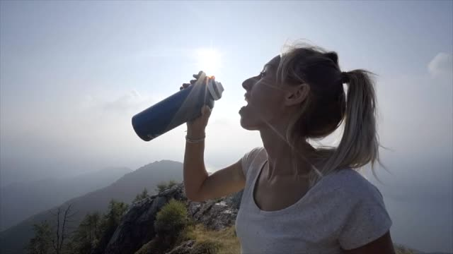 hiker woman drinking on mountain trail from water bottle  after long hike to reach the summit, beautiful sun rising on top of swiss alps - zucca legenaria video stock e b–roll