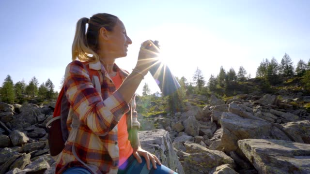 hiker woman drinking on mountain trail from water bottle. woman hiking in the swiss alps having a break and drinking from bottle - ventenne video stock e b–roll
