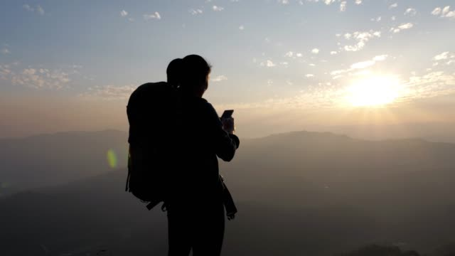 hiker woman using mobile phone for take a photo on the top of mountain in sunset time , dolly movement , slow motion - guardare il paesaggio video stock e b–roll