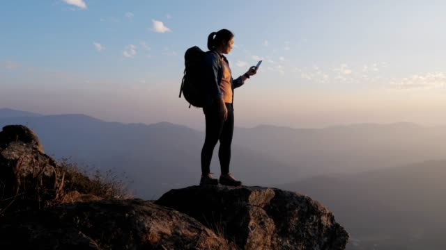 hiker woman using mobile phone for take a photo on the top of mountain in sunset time , dolly movement , slow motion - in cima video stock e b–roll